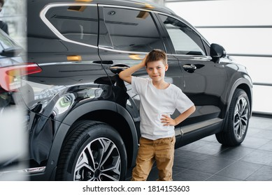 At a car dealership, a happy boy stands near a new car before buying it. Car purchase