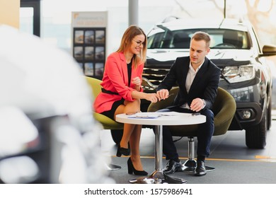 Car dealership sales person at work concept. Portrait of young sales representative wearing formal wear suit, showing vehicles at automobile exhibit center. Close up, copy space, background.