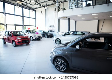 Car dealership showroom interior with brand new vehicles for sale.