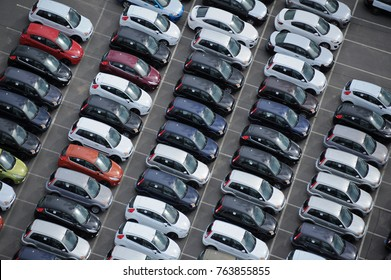 car dealership yard at a port, cars waiting to get through customs
