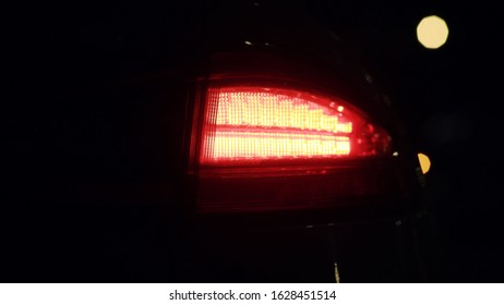 Car detail. Modern new white car tail lights shining red close-up. Rear back lights of sports luxury car flashing in the dark at open parking space.