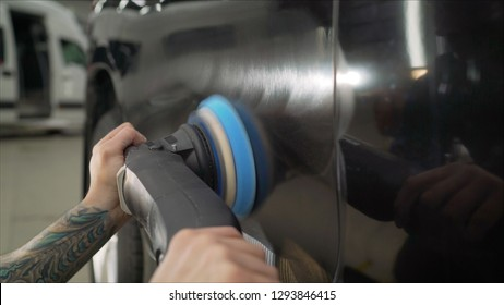 Car detailing - Hands with orbital polisher in auto repair shop. Polished black car.