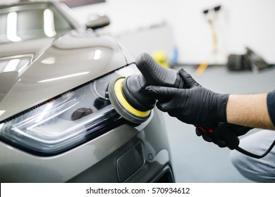 Car detailing - Hands with orbital polisher in auto repair shop. Selective focus.