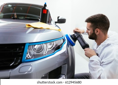 Car detailing - Hands with orbital polisher in auto repair shop. Front lights protected with isolation blue tape. Selective focus.