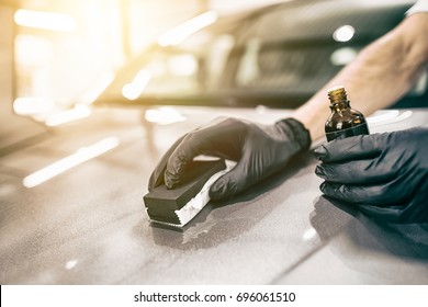 Car detailing - Man applies nano protective coating to the car. Selective focus.