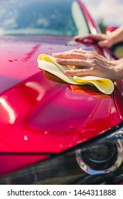 Car detailing - the man holds the microfiber in hand and polishes the car. Selective focus. Car detailing series : Worker cleaning red car.