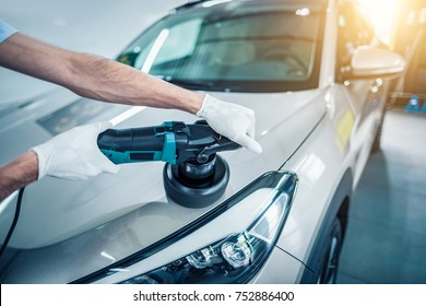 Car detailing - Man holds a polisher in the hand and polishes the car. Selective focus.
