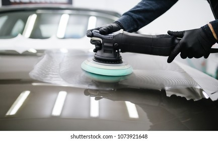 Car detailing - Man with orbital polisher in repair shop polishing car. Selective focus. - Shutterstock ID 1073921648