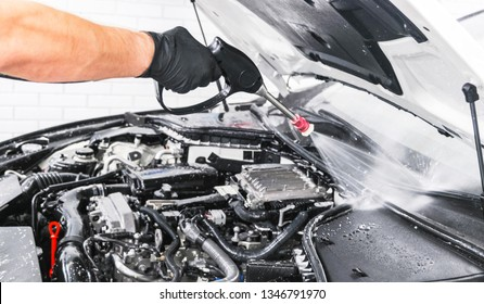 Car detailing. Manual wash engine with pressure water. Washing car engine with water nozzle. Car wash man worker cleaning vehicle. Man spraying pressure washer for car wash