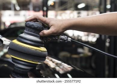 Car detailing series: Closeup of worker's hand using tool waxing black car hood in garage