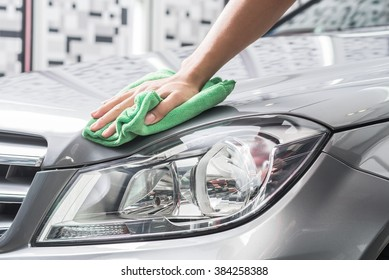 Car detailing series : Worker cleaning gray car
