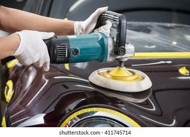 Car detailing series : Worker polishing brown car
