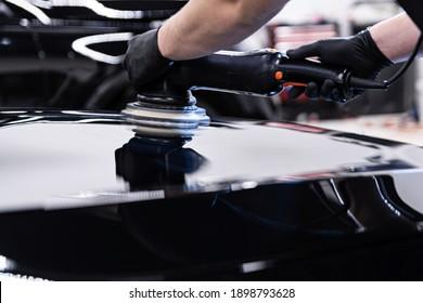 Car detailing studio worker polishing car paint