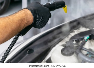 Car detailing. Car washing cleaning engine. Cleaning car engine using hot steam. Hot steam engine washing. Soft lighting. Car wash station worker cleaning vehicle. Vehicle wash concept