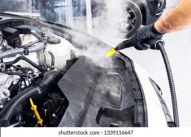 Car detailing. Car washing cleaning engine. Cleaning car using hot steam. Hot Steam engine washing. Soft lighting. Car wash man worker cleaning vehicle.