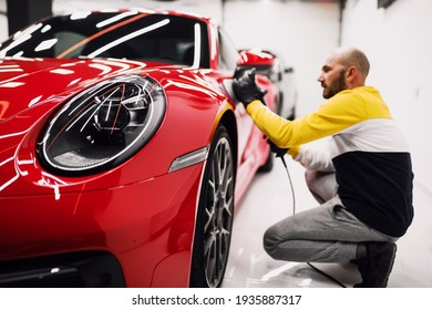Car detailing - Worker with orbital polisher in auto repair shop. Selective focus.