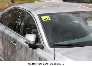 Ein Auto mit Behindertenzeichen steht auf einer Stadtstraße.