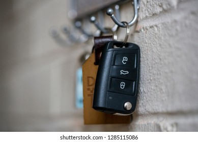 Car and door keys hang on a wall in a house