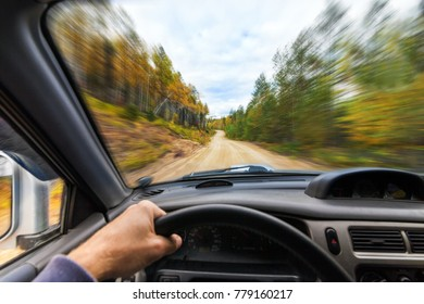 Car drive trough autumn forest by a dirt road. View from driver's eyes