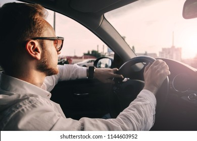 car driver is a businessman in sunglasses. trip at sunset.