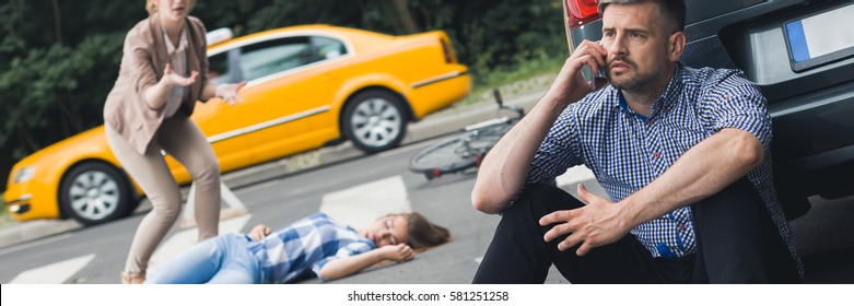 Car driver calling an ambulance, stressed woman trying to help an unconscious bike driver after accident