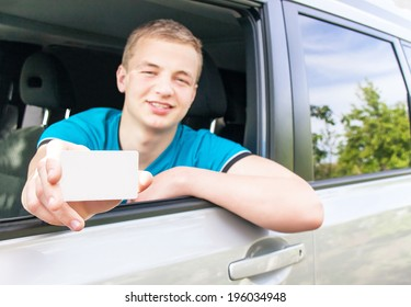 Car driver. Caucasian teen boy showing an empty white card for your message in the new car. Happy smiling young man behind the wheel. Travel and rental concept. Close up, outdoor.