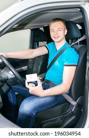 Car driver. Caucasian teen boy fastening seat belt and showing driver license in the car. Happy smiling young man behind the wheel. Travel and rental concept. Close up, outdoor.