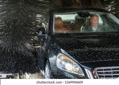Car with driver inside on a auto carwash. Automatic washing of a black luxury car. Part of a car in white soapy foam.