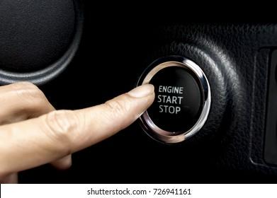 Car driver starting the engine keyless.