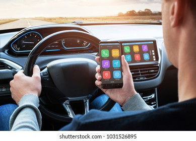 Car driver use smart phone with smart car app and use connection with car infotainment system while driving.