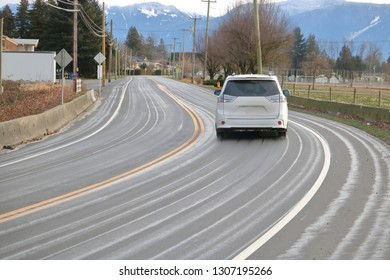 A car drives past a tight corner after the asphalt road has had liquid brine sprayed on the surface to deal with icy hazardous conditions.