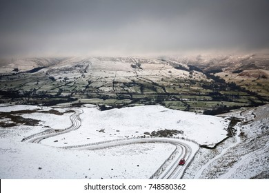 A car drives up a snow covered mountain road in winter. Edale valley, Peak District, UK