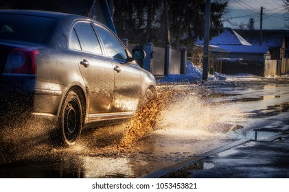 The car drives through a puddle, splashing water