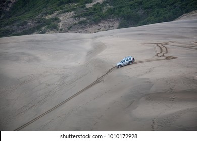Car driving down the steep hill on a sandy beach in Oregon Coast.