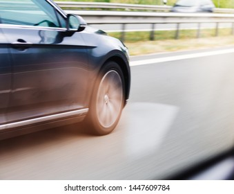 Car driving fast on highway motion blur