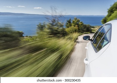 Car driving fast on a mountain road towards the sea