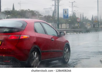 The car is driving at high speed on a wet road, splashing rain, raindrops and circles on the water. Israel, Rain, Flooding on the road