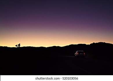 Car driving in Joshua Tree National Park in the night, sunrise, sundown, colorful sky