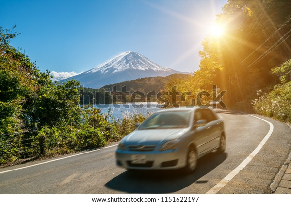 Car driving near Mt Fuji in Japan with motion blur showing rapid movement on a highway road at Lake Kawaguchiko. Concept of road trip travel, rental cars and tourism in Japan.