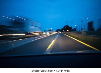 Car driving at night on highway. Driver view and motion blur.