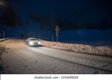 car driving on dangerous road at night with fresh snow