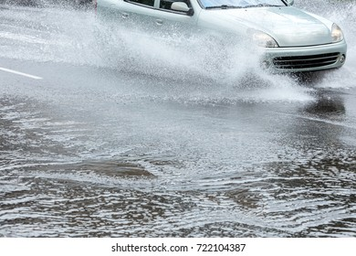 car driving on flooded city road through puddles creating water splashes