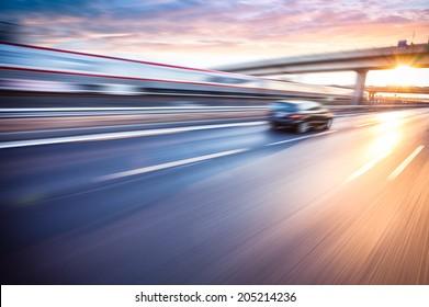Car driving on freeway at sunset, motion blur