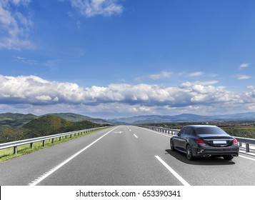 Car is driving on the high-speed highway, on the background of blue cloudy sky.