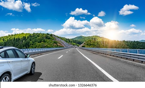 Car driving on highway surrounded by picturesque mountains.
