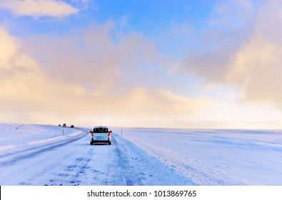 Car driving on the icy road in winter on the plateau in Iceland.