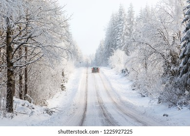 Car driving on a winter road in the woods