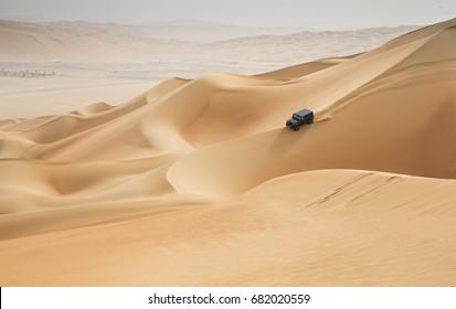 car driving in Rub al Khali Desert at the Empty Quarter, in Abu Dhabi, United Arab Emirates