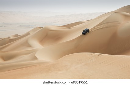 car driving in Rub al Khali Desert at the Empty Quarter, in Abu Dhabi, United Arab Emirates