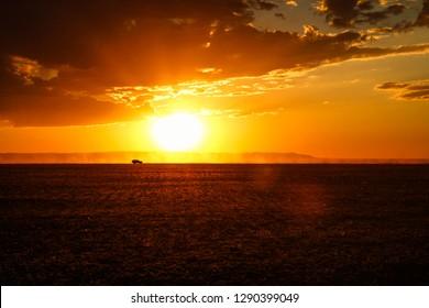 Car driving thorugh Gobi Desert with dramatic sunset / dawn and orange illuminated stunning clouds and red sky (Gobi Desert, Mongolia, Asia)